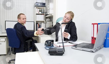 Too many calls stock photo, A businesswoman accepting a third telephone from a colleague, already talking to different people on various lines by Corepics VOF