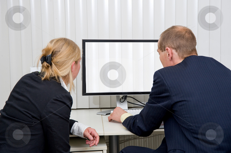 Staring at blinds stock photo, Two colleagues staring at a monitor with blinds in a blinded office by Corepics VOF