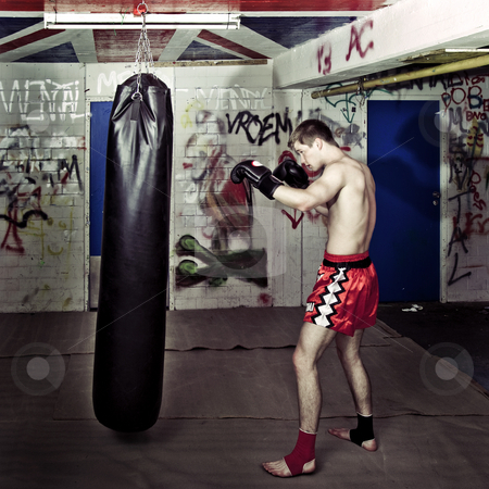Punching boxer stock photo, Cross processed image of a boxer practising in a basement with a boxing bag by Corepics VOF