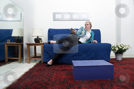 Boredom stock photo, Young woman lying outstetched on a couch, looking very bored with a remote control in her hands by Corepics VOF