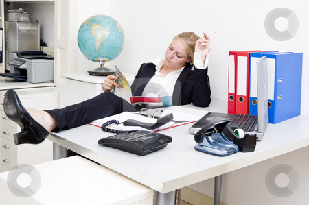 Lazy receptionist stock photo, Lazy receptionist, reading a glossy magazine and smoking a cigarette, after having put the phone off the hook by Corepics VOF