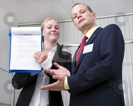Contract stock photo, Two business people proudly showing a contract for an important business deal by Corepics VOF