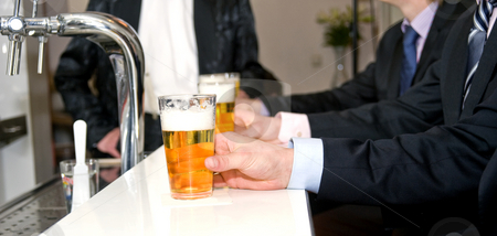 Beers on a Bar stock photo, A row of people holding their beers on a bar with a shallow depth of field by Corepics VOF