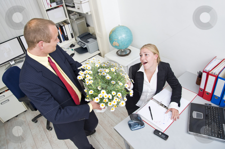 Business gift stock photo, Senior manager giving his younger female associate a large flower pot with white daisies by Corepics VOF