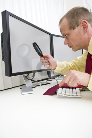 Analyzing computer data stock photo, Businessman seriously analyzing data on a computer monitor using a magnifying glass, with his left index finger hovering above the escape key to interrupt the process.