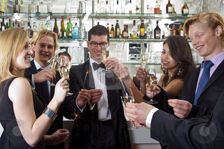 Toasting on a new Years Eve Party stock photo, Several people toasting with champagne on new years eve while holding sparkling sticks by Corepics VOF