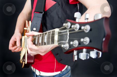 Guitarist stock photo, A guitarist working the fretboard and strings. Selective focus on the musicians left hand by Corepics VOF