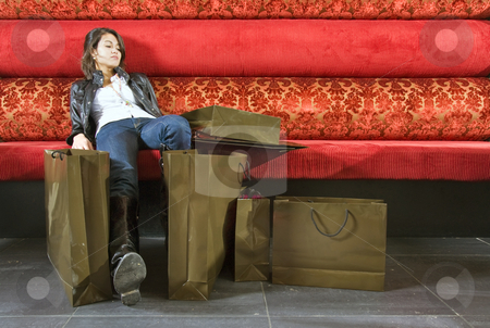 Woman sitting in a lounge after shopping stock photo, A young woman resting in a lounge after shopping with her stuffed shopping bags beside her by Corepics VOF