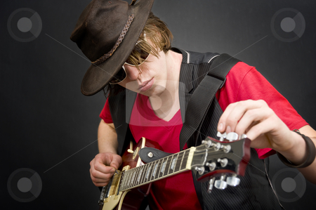 Tuning a guitar stock photo, A cool looking guitar player tuning his instrument by Corepics VOF