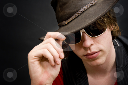 Cool bloke stock photo, A funky looking man lifting the rim of his old leather hat by Corepics VOF