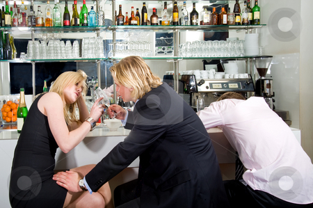 Flirting at a bar stock photo, Three young adults sitting at a bar; one sleeping, the others flirting with each other by Corepics VOF