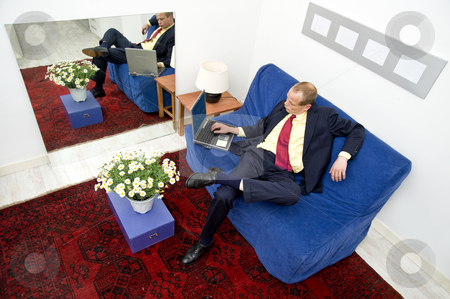 Private finances at home stock photo, Businessman, making himself comfortable on a couch at home, going over his private stock on a laptop by Corepics VOF