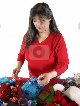 Woman Wrapping Present stock photo, An adult female wraps a gift with ribbons and bows. Over white. by Robert Gebbie