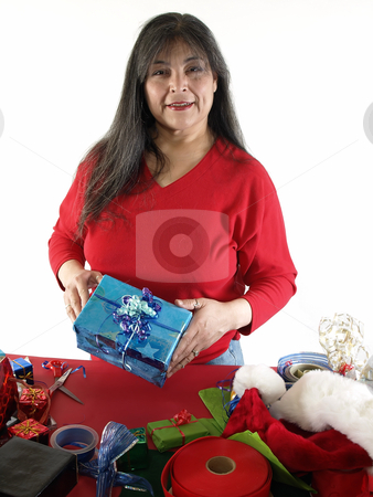 Finished Wrapping stock photo, An adult female wraps a gift with ribbons and bows. Over white. by Robert Gebbie