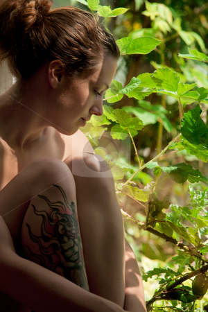 Young adult woman sitting in front of a window thinking stock photo, Portrait of a young adult woman being naked in a sunny environment by Frenk and Danielle Kaufmann