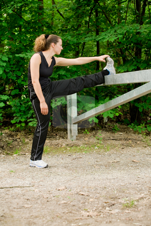 Young adult woman stretching her leg on a forrest road stock photo, Outside portrait of a woman stretching after jogging by Frenk and Danielle Kaufmann