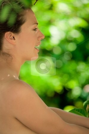 Womand standing outside in a sunny green environment stock photo, Outside portrait of a young adult woman by Frenk and Danielle Kaufmann