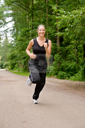 Sportive young woman running over a forrest road stock photo, Young adult jogging on a forest road by Frenk and Danielle Kaufmann