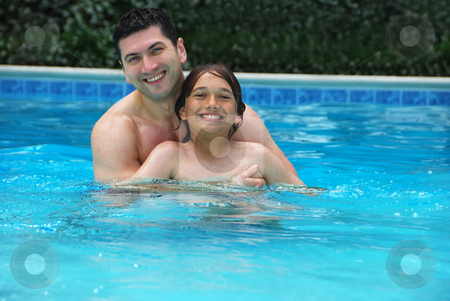 Son and Dad Enjoying Pool stock photo, Son and dad enjoying the swimming pool. by Denis Radovanovic