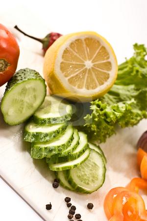 Vegetarian diet stock photo, Vegetable mix: lettuce, onion, lemon, cucumber on the board by Gennady Kravetsky
