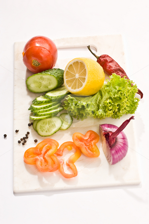 Vegetarian diet stock photo, Vegetable mix: lettuce, onion, lemon, cucumber on the board by Gennady Kravetsky