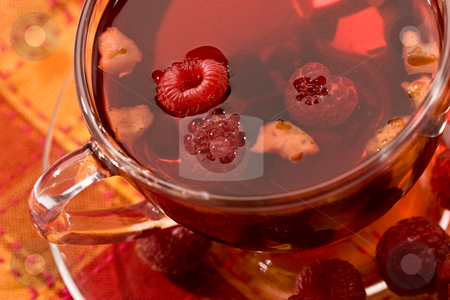 Fruit tea stock photo, Cup of tea with raspberry syrup and some raspberries by Gennady Kravetsky