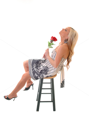 Pretty girl enjoying life. stock photo, Beautiful young teenager sitting in an black and white dress on a green bar chair with a red rose in her hand, long blond hair, and enjoying life. by Horst Petzold