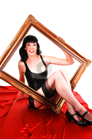 Framed girl in lingerie. stock photo, Pretty tall girl sitting in lingerie on red silk, holding an old picture frame in her hand and the legs going trough the frame. by Horst Petzold