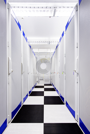 Data Center Aisle stock photo, Clean suite in a data center with the perforated doors of server racks by Corepics VOF