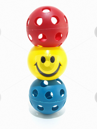 Stacked Balls stock photo, Three balls stacked on top of each other, one with a yellow smiley face. Isolated on white. by Robert Gebbie