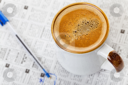 Coffee and newspaper stock photo, Hot cup of coffee on a newspaper with pen by Steve Mcsweeny