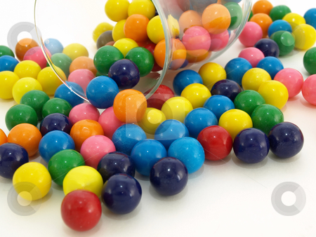 Bubblegum Spill stock photo, A colorful variety of gumballs spilled from a glass on a white background. by Robert Gebbie