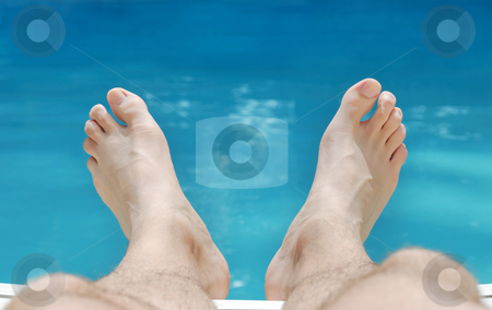 Relaxing Feet in Summer stock photo, Two feet relaxing in sunlight with swimming pool water in the background. by Denis Radovanovic