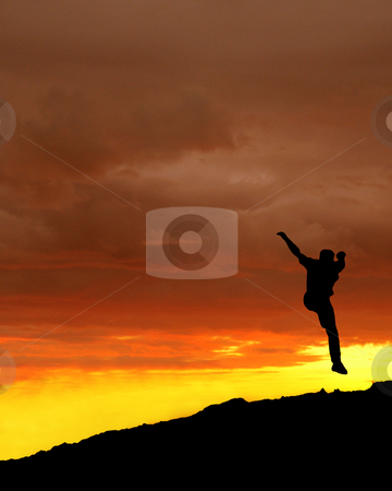 Jump in the sun - A climber reaches the summit stock photo, Man jumps in sunset on the summit of a mountain by Reinhart Eo