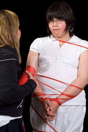 Tied Up stock photo, A young girl being tied up with rope by another girl by Richard Nelson