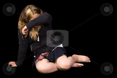 Child Abuse stock photo, A young girl cowering on the floor trying to protect herself from some abuse, isolated against a black background by Richard Nelson