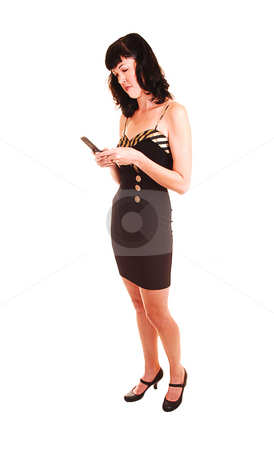 Woman on the phone. stock photo, An tall young woman in a black dress standing an dialing on the cell phone, in the studio for white background. by Horst Petzold