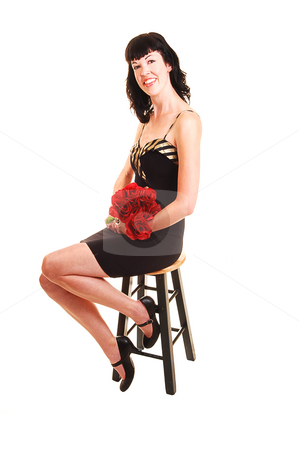 Woman sitting on chair. stock photo, An tall young woman in a black dress sitting on a chair with red roses in her hand in the studio for white background. by Horst Petzold