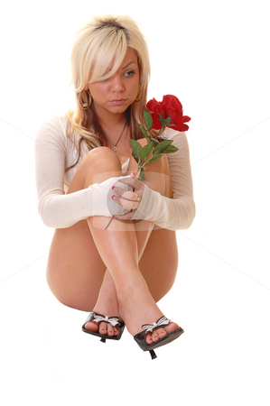 Woman sitting on floor. stock photo, Young woman in panties and high heels sitting on the floor in the studio holding a red rose in her hand, for white background. by Horst Petzold