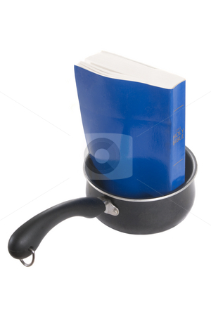 Cooking the Books stock photo, Paperback Bible in Sauce Pan, Isolated on a white background. by Steve Carroll