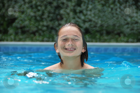Smiling Teen in Swimming Pool stock photo, Smiling teen boy in swimming pool surrounded with white flower bushes in the background. by Denis Radovanovic