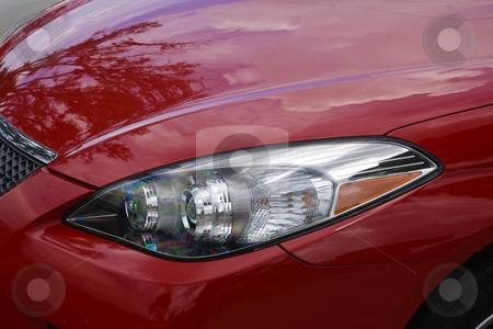 Automotive Headlight stock photo, Headlight of a red sports car. by Steve Carroll