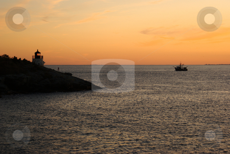 Sunset Ship and Lighthouse stock photo, Silhouette of a cargo ship passing the lit Castle Hill lighthouse at sunset. by Daniel Rosner