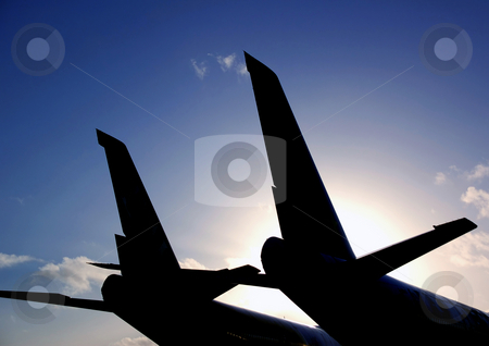 Silhouette Jet Wings stock photo, Silhouette of tail fins of a jet plane with deep blue sky at dusk by Robert Ford