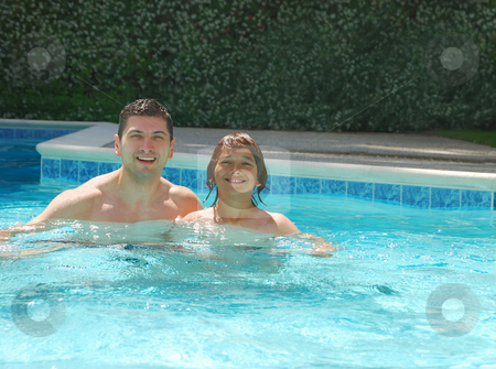 Dad and Son Enjoying Swimming Pool stock photo, Dad and son enjoying the swimming pool on a sunny summer day. by Denis Radovanovic