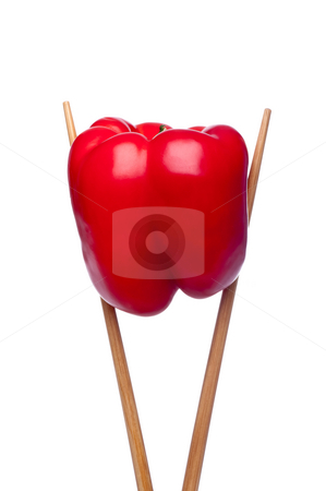 Red pepper in chopsticks stock photo, A vertical image of a red bell pepper in chopsticks on a white background by Vince Clements