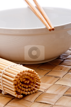 A vertical image of a pair of chopsticks on a white bowl stock photo, A vertical image of a pair of chopsticks on a white bowl with a suhi rolling mat on a weaved placemat by Vince Clements
