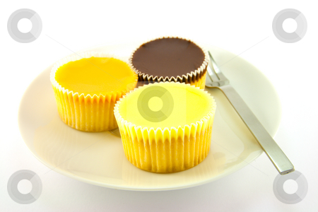 Three Cup Cakes stock photo, Three delicious looking cup cakes resting on a white plate with a fork on a plain background by Keith Wilson