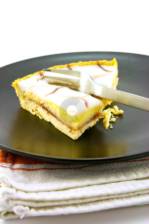 Bakewell Tart stock photo, Delicious looking iced bakewell tart on a black plate with a fork and a plain background by Keith Wilson