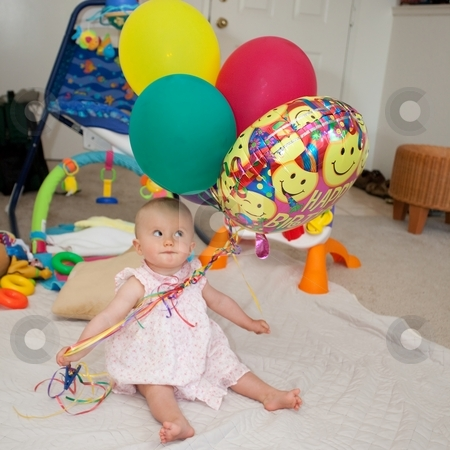 Balloons stock photo, Caucasian baby girl playing with colorful balloons on a floor. by Mariusz Jurgielewicz